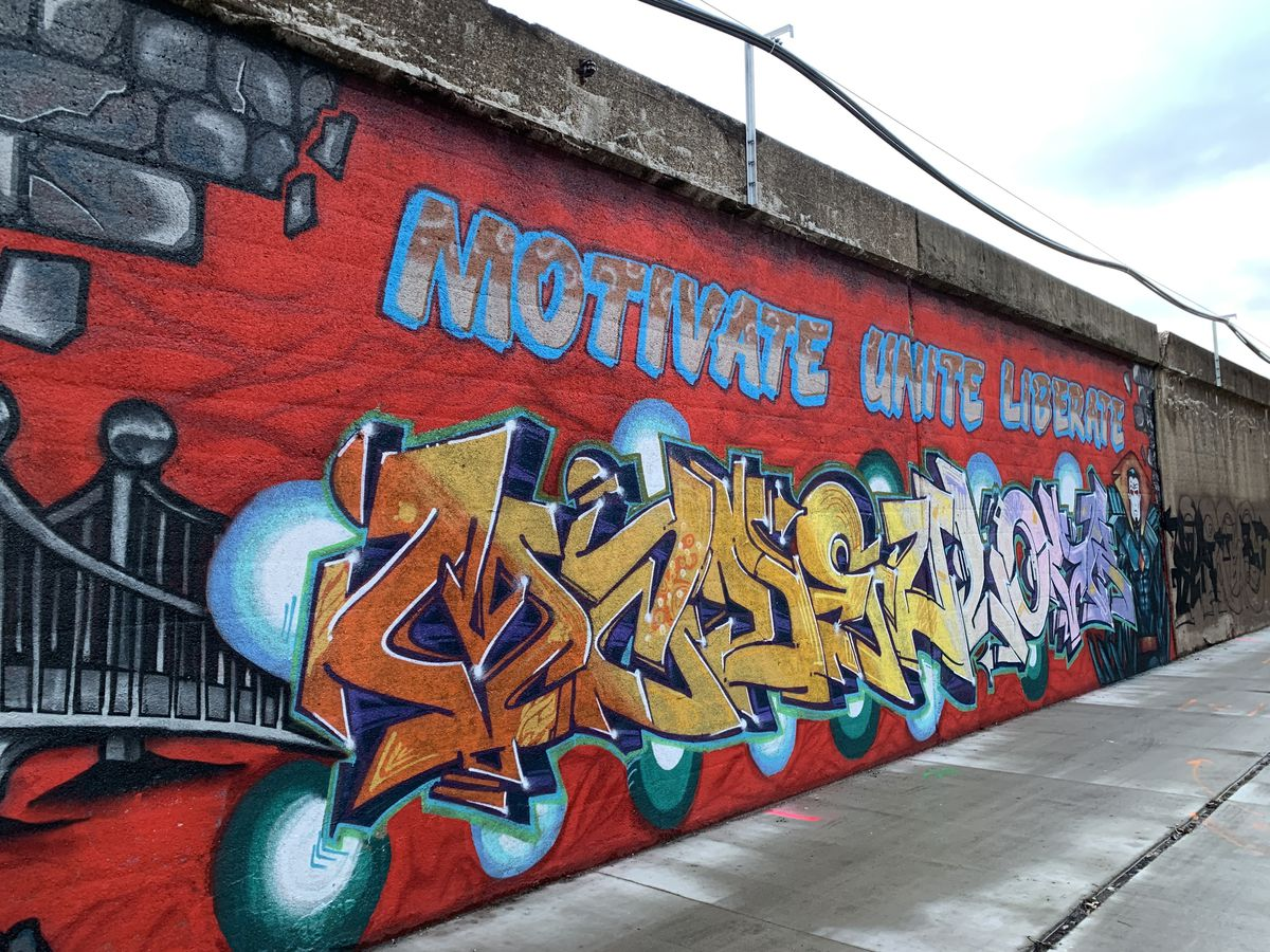 """This mural by the Made You Look Group is a call to action, with the words """"Motivate,"""" """"Unite"""" and """"Liberate"""" above wildly stylized lettering. There's a bridge visible in the background, and a blue comic book-like figure stands to the right."""