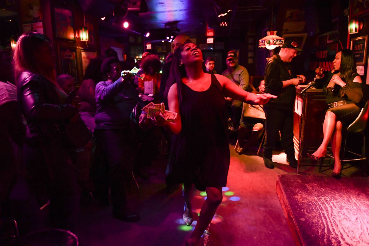 Patrons crowd a bar under red and blue lights as draq queen Miss Lisa Lisa dances in a black dress and collects dollars from the crowd.
