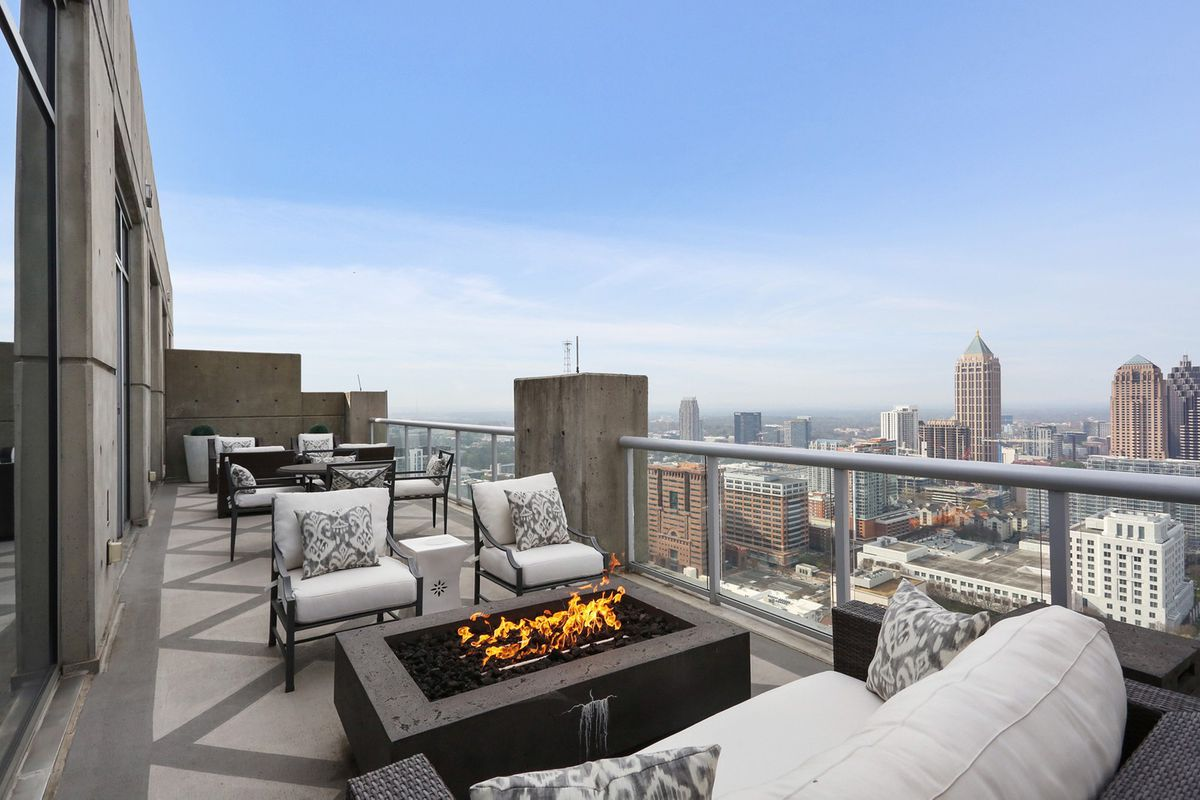 A huge terrace with a fire pit and a lot of seating.