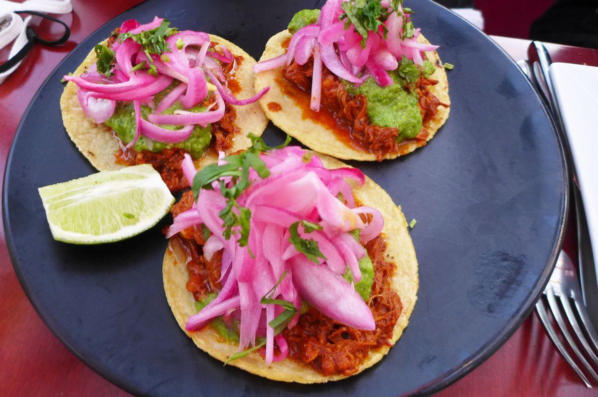 Three tacos on flattened corn tortillas with shredded pork and pink onions.