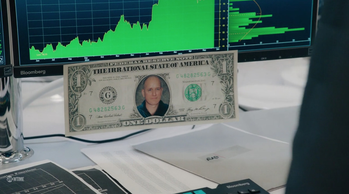 A dollar bill taped to Dollar Bill's desk with his face on it