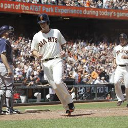 San Francisco Giants' Buster Posey, center, and Brett Pill, right, score on a triple by Joaquin Arias during the sixth inning of a baseball game against the San Diego Padres in San Francisco,  Sunday, April 29, 2012. San Francisco won 4-1.