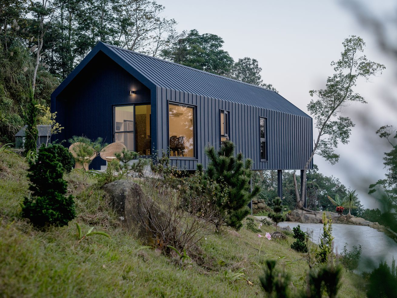Pitch-roofed black-clad house on stilts cantilevering over mountain.