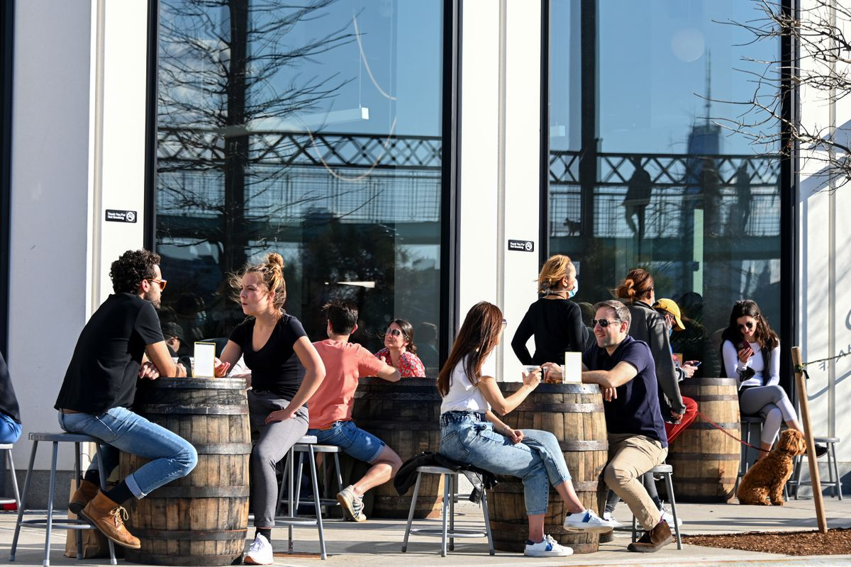 People sit at a restaurant's outdoor tables in Williamsburg with a view of One World Trade Center in the window's reflection on March 26, 2021 in the Brooklyn borough of New York City.
