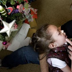 Callahan Williams holds Eliza in her bedroom next to the good-deeds Christmas tree at their Bountiful home last week. The 4-year-old is dying of a rare disease.