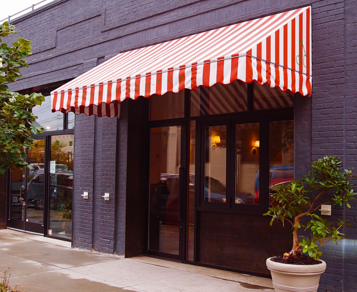 The front of a business, with dark-colored brick walls and a red and white striped awning