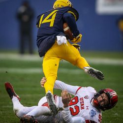 West Virginia Mountaineers running back Tevin Bush (14) cannot escape the open field tackle of Utah Utes place kicker Hayes Hicken (92) at the Zaxby's Heart of Dallas Bowl between the Utah Utes and the West Virginia Mountaineers in Dallas Texas on Tuesday, Dec. 26, 2017.