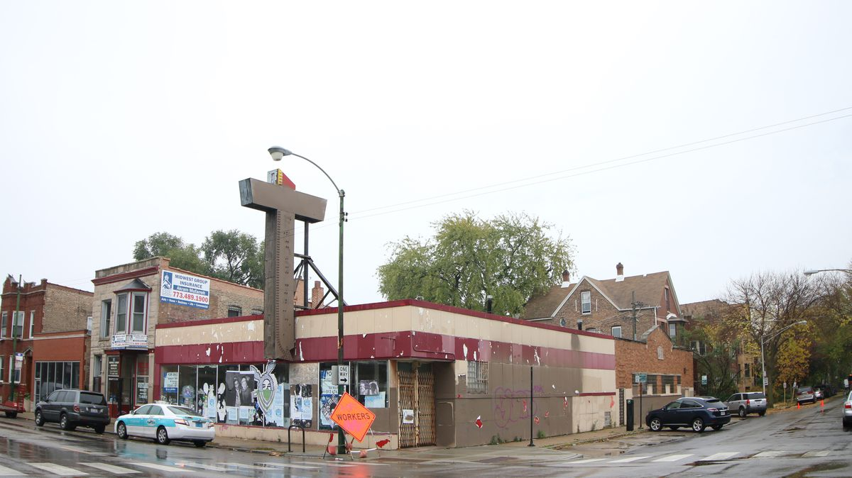 An exterior view of a building on the corner of a street block in a city. The building is in poor condition and has a large metal sign in front of it.