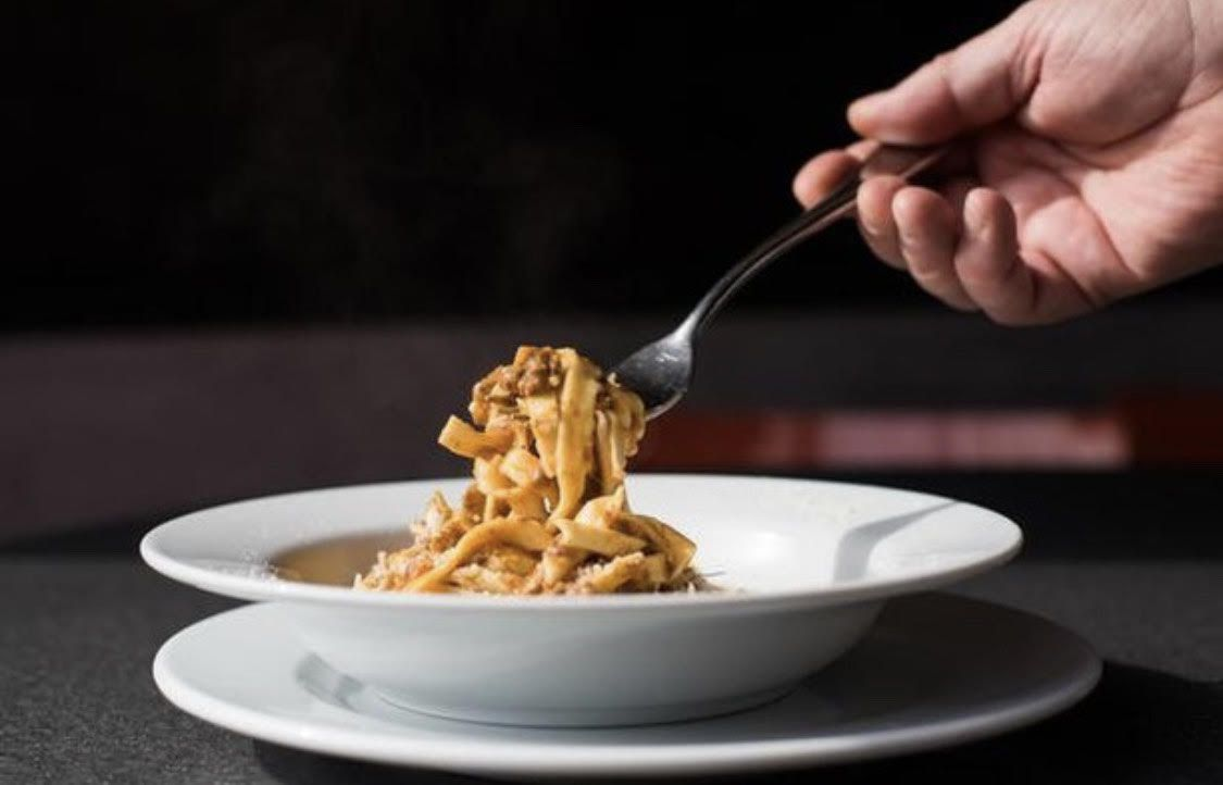 A bowl of fettuccine with a fork lifting up the noodles