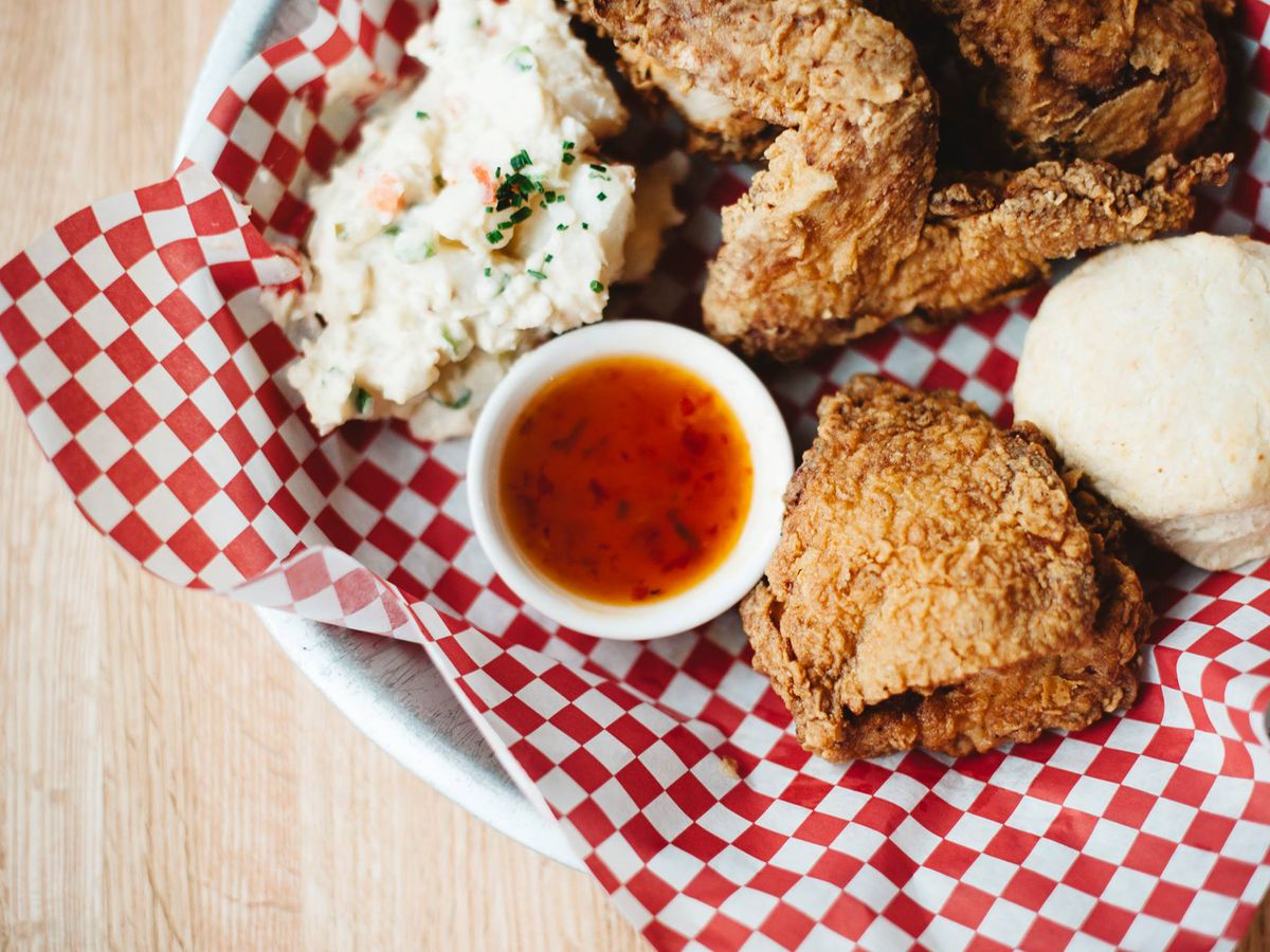 Overhead view of fried chicken, mashed potatoes, slaw, and dipping sauce on a red-and-white checkered paper on a white plate.