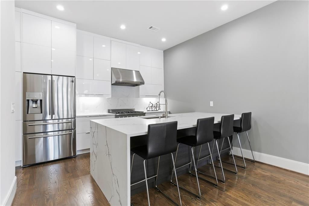 A white and gray kitchen with black seats and stainless appliances.