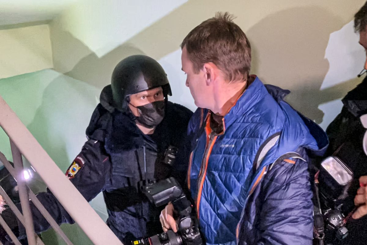 A police officer pushes photographers from a door of the apartment where Oleg Navalny, brother of jailed opposition leader Alexei Navalny lives in Moscow, Russia, Wednesday, Jan. 27, 2021.