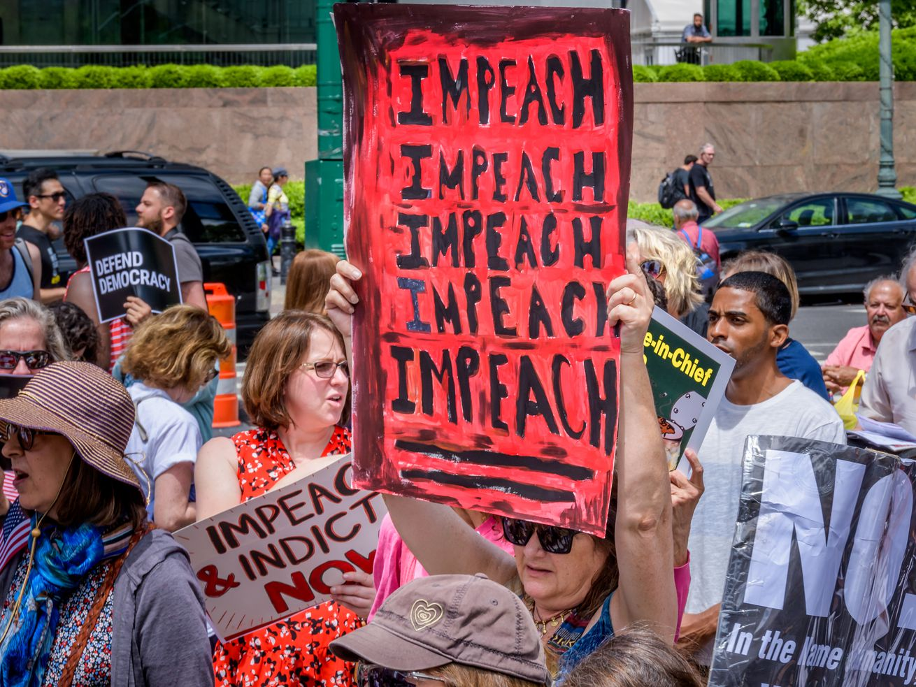 "New Yorkers hoist handmade signs; the largest is red and black, and says ""impeach"" five times."