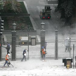 Workers clean the dust and dirt from the sidewalks and entry way at the south gates to Temple Square after the old Key bank building was demolished in downtown Salt Lake City by explosives. August 17, 2007.