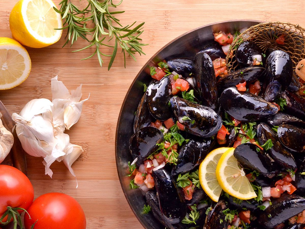 A large bowl of mussels with chopped tomatoes and herbs, on a wood table with some of the raw ingredients