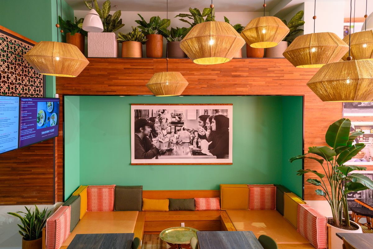 a photograph of Immigrants at the table hangs on a wall surrounded by lounge seating