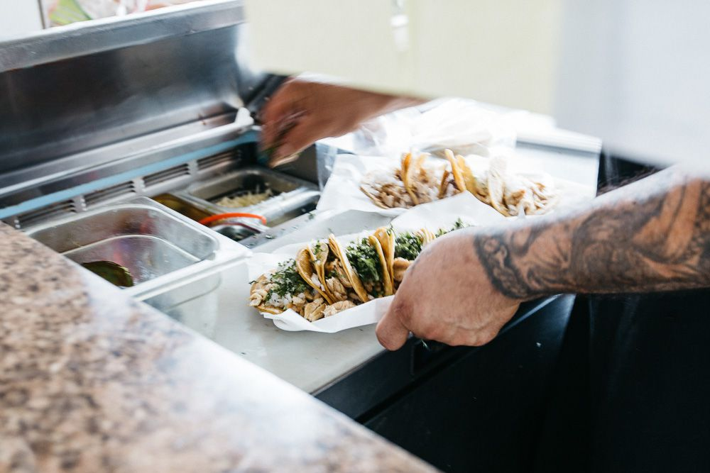 Hands pick up a plate of tacos in the kitchen at El Rey.