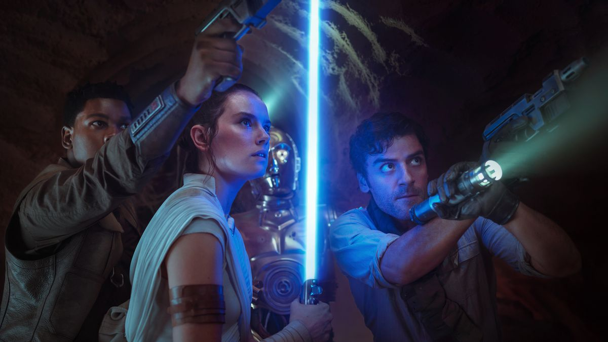 Finn aiming his gun upward, Rey holding her blue lightsaber straight upward, and Poe aiming a gun and flashlight upward, with C-3PO standing behind them, in Star Wars: The Rise of Skywalker