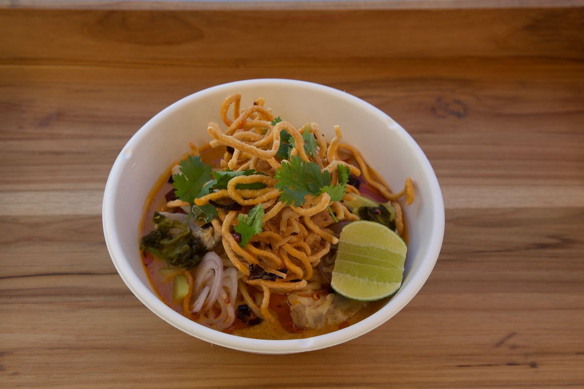 Kin Khao's khao soi: noodles in curry broth topped with crispy noodles, fresh herbs, and lime