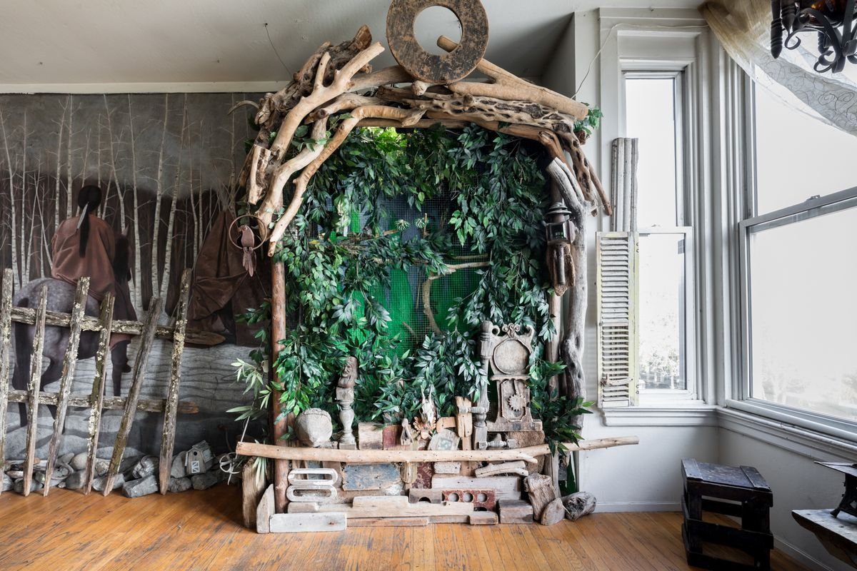 The interior of a room with an altar constructed out of tree branches and construction materials. On the wall in back of the altar is a mural depicting people riding donkeys into a forest full of trees with thin white branches.