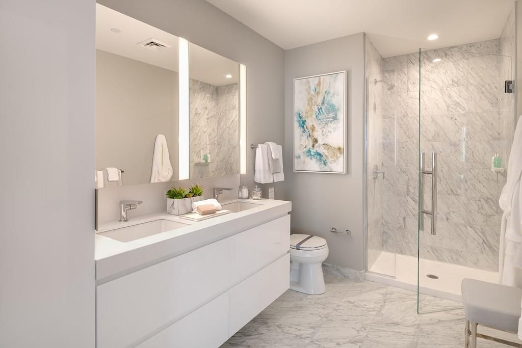 A modern marble bathroom with a glass-door shower.