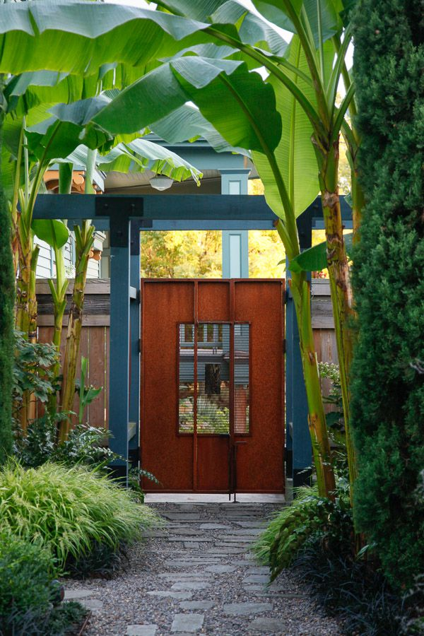 Tall, leafy plants create a tunnel-like space that guides the visitor forward.