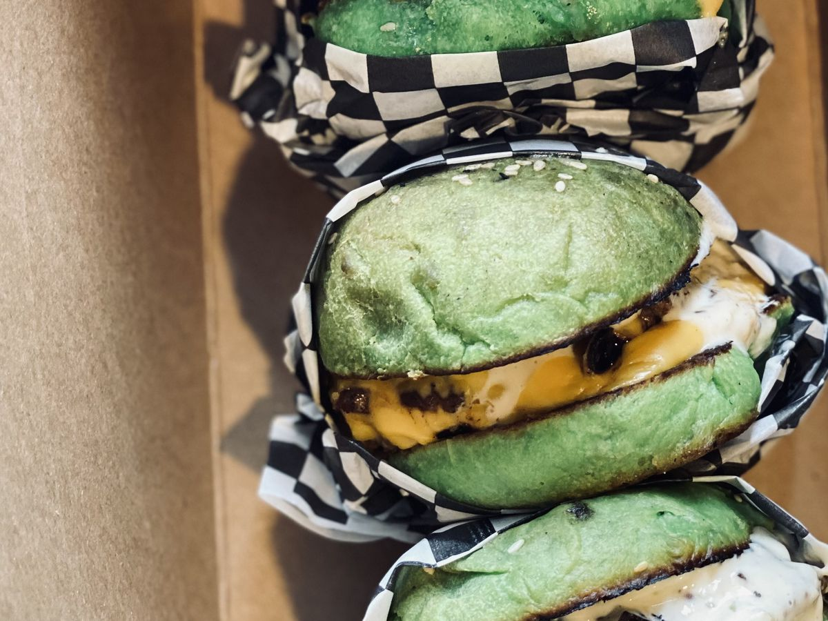 Three cheeseburgers with green buns are wrapped in checkered paper.