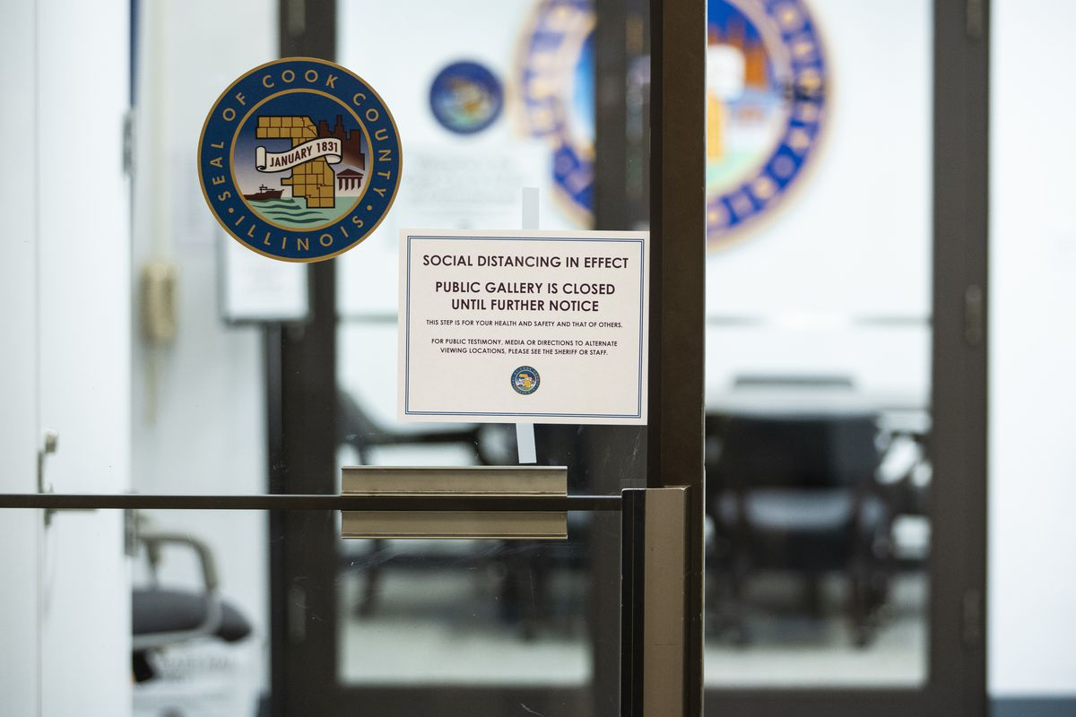 """""""Social distancing in effect"""" signs posted at the Cook County Board of Commissioners meeting room in March."""