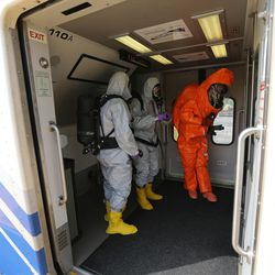 """Emergency personnel in chemical suits check a FrontRunner train during """"Hell on Wheels,"""" a full-scale, two-day, emergency protection and response drill at the Salt Lake Central Station on Tuesday, Aug. 8, 2017. The drill included emergency personnel from the Utah Transit Authority, the FBI, Salt Lake County Emergency Management, the West Valley and Salt Lake City fire departments, University of Utah Emergency Management, the University of Utah Police Department, Amtrak, Union Pacific, Murray Victim Advocates and Utah State Medical Examiner's Office. The drill simulated multiple terrorists entering the Salt Lake Valley and dividing up."""