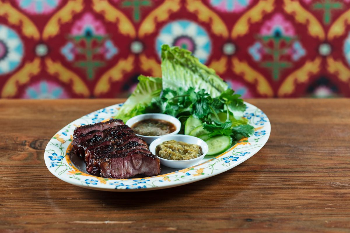 A picture of a chunk of pork steak with pieces of lettuce, herbs, and two dipping sauces on the side