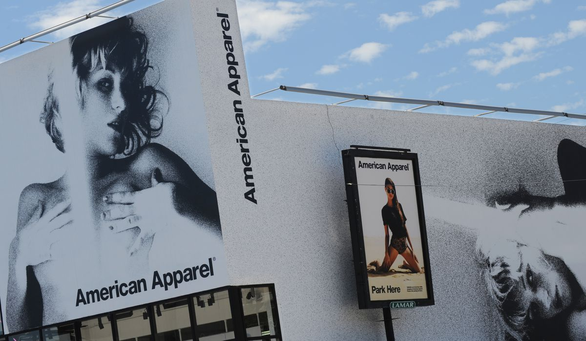The outside of an American Apparel store, which shows a photo of a topless young woman.