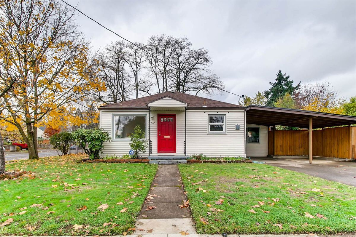 Small bungalow home with carport and front yard.