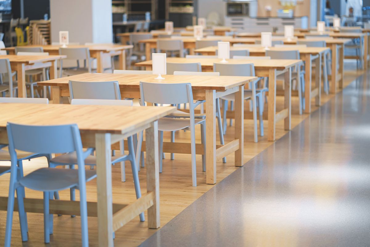 Blond wood tables and chairs close together, in a college dining hall