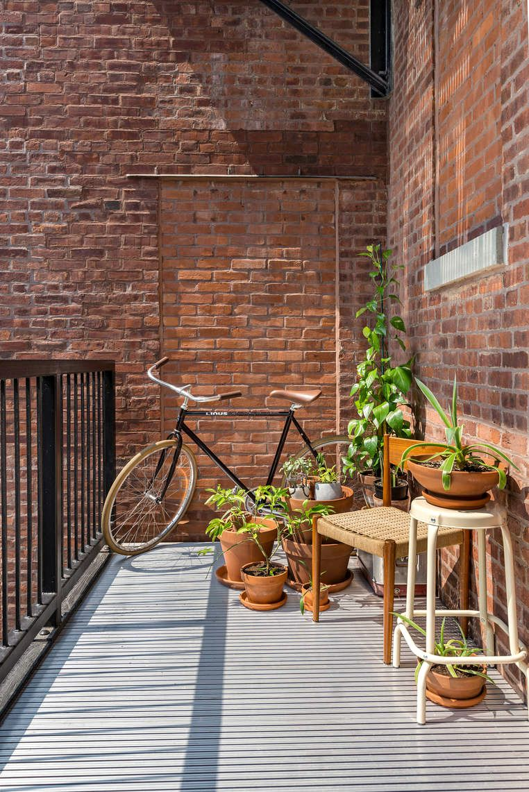 A private terrace with exposed brick, iron railings, a bike, two chairs, and several planters.