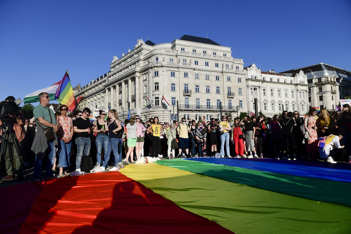 People unfurl a rainbow flag during an LGBT rights demonstration in front of the Hungarian Parliament building in Budapest, Hungary on June. 14, 2021.