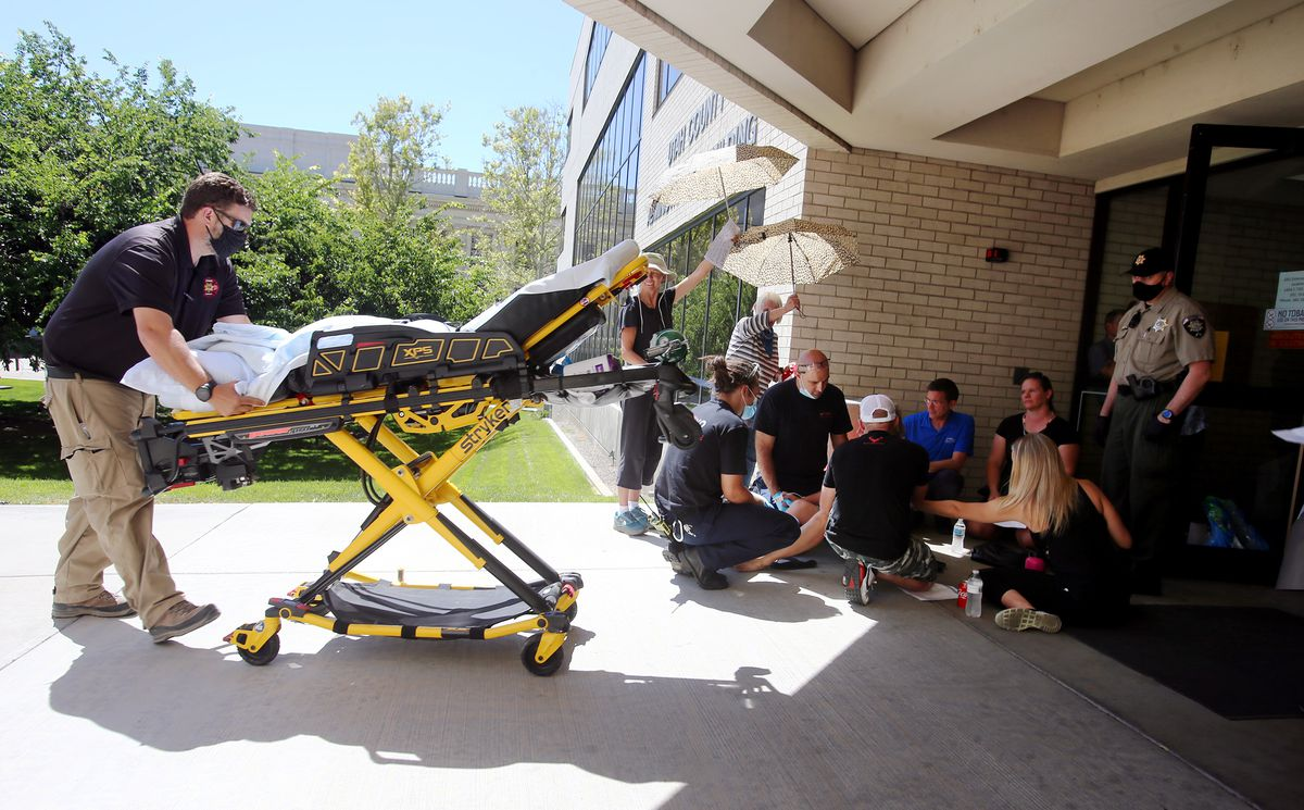 Paramedics take a woman to an ambulance after she collapsed following a Utah County Commission meeting in Provo on Wednesday, July 15, 2020. The woman reportedly had been trying to speak to Tanner Ainge, the commission's chairman, about a state mandate to wear masks in K-12 schools and felt like she wasn't being listened to.