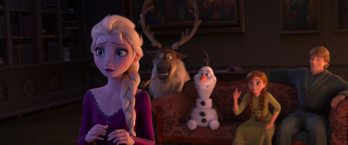 in the middle of a charades game, elsa turns around, concerned. she faces away from her friends. on the couch behind her, sven the reindeer, anna, olaf, and kristoff are all smiling and happy