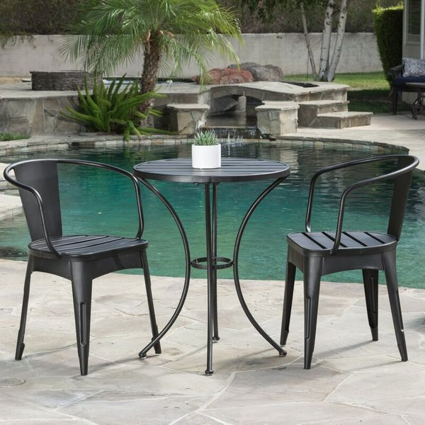 2 black chairs and table by the side of a pool
