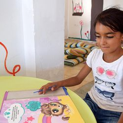 Cidra Al-Hamdan, 8, from Damascus, Syria, reads a book in the kindergarten at the Kyllini refugee camp in Myrsini, Greece, July 11, 2016. The camp was previously a luxury resort before it fell into disrepair and was later turned into a refugee camp.
