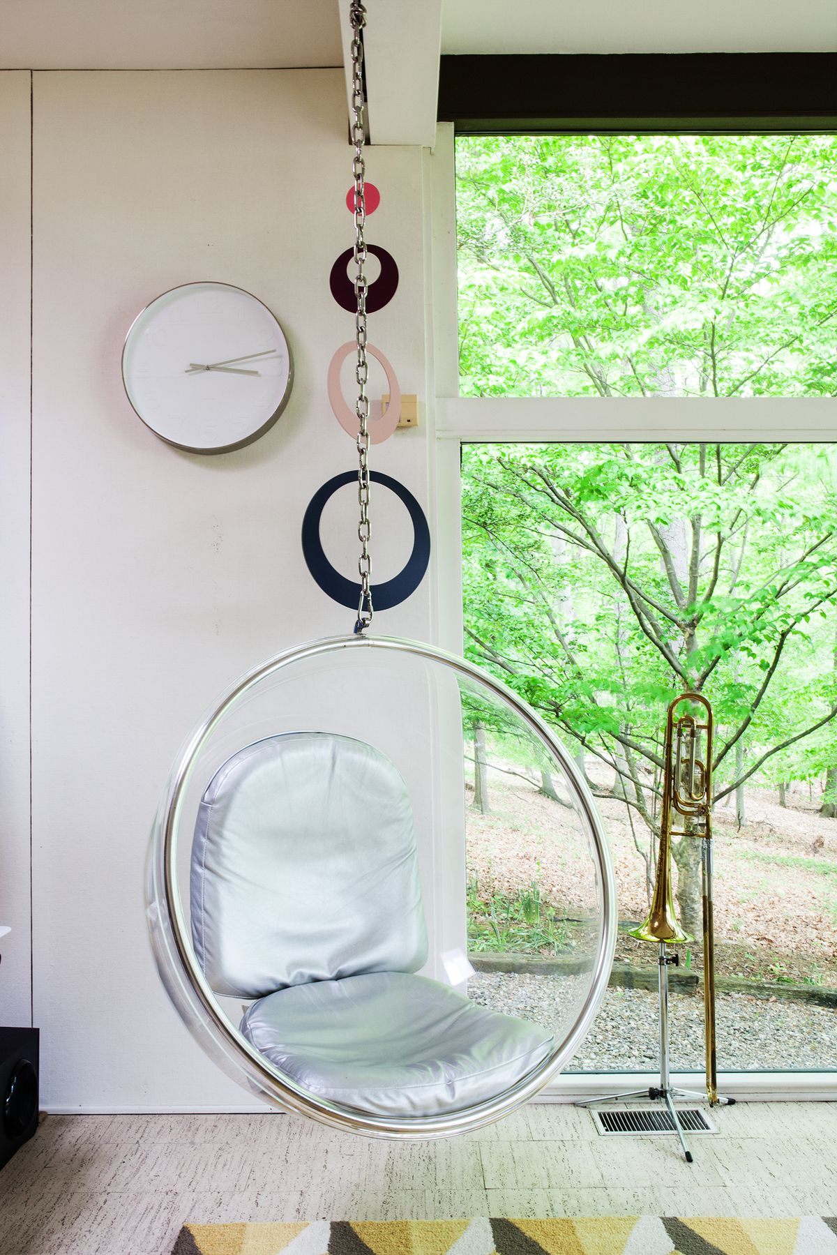 A round, clear-plastic chair with silver cushions hangs in the office.