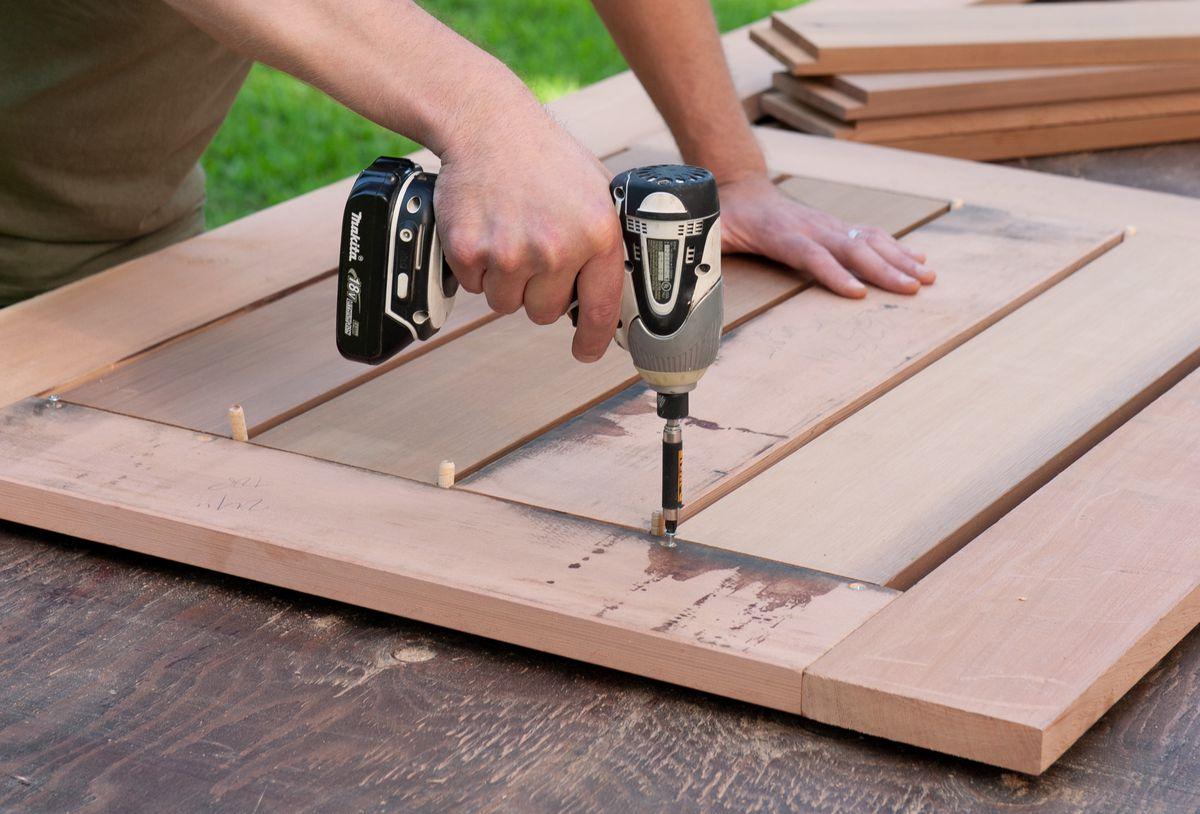 Man Attaches Slats Of Picnic Table