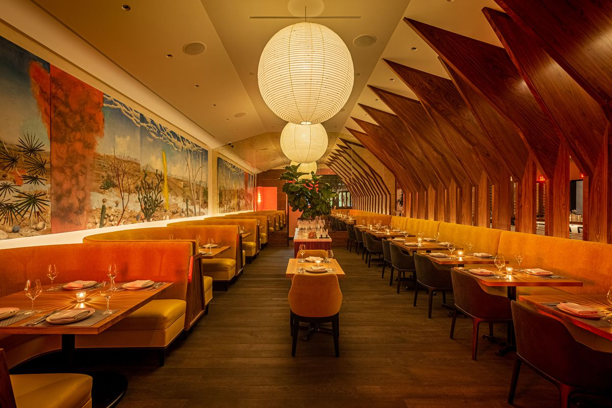 A long restaurant with orange booths at left and bulbous lights overhead.