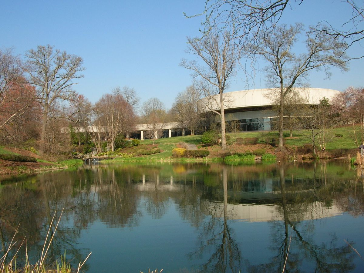 In the foreground is a body of water. In the distance is a building surrounded by trees that have bare branches.