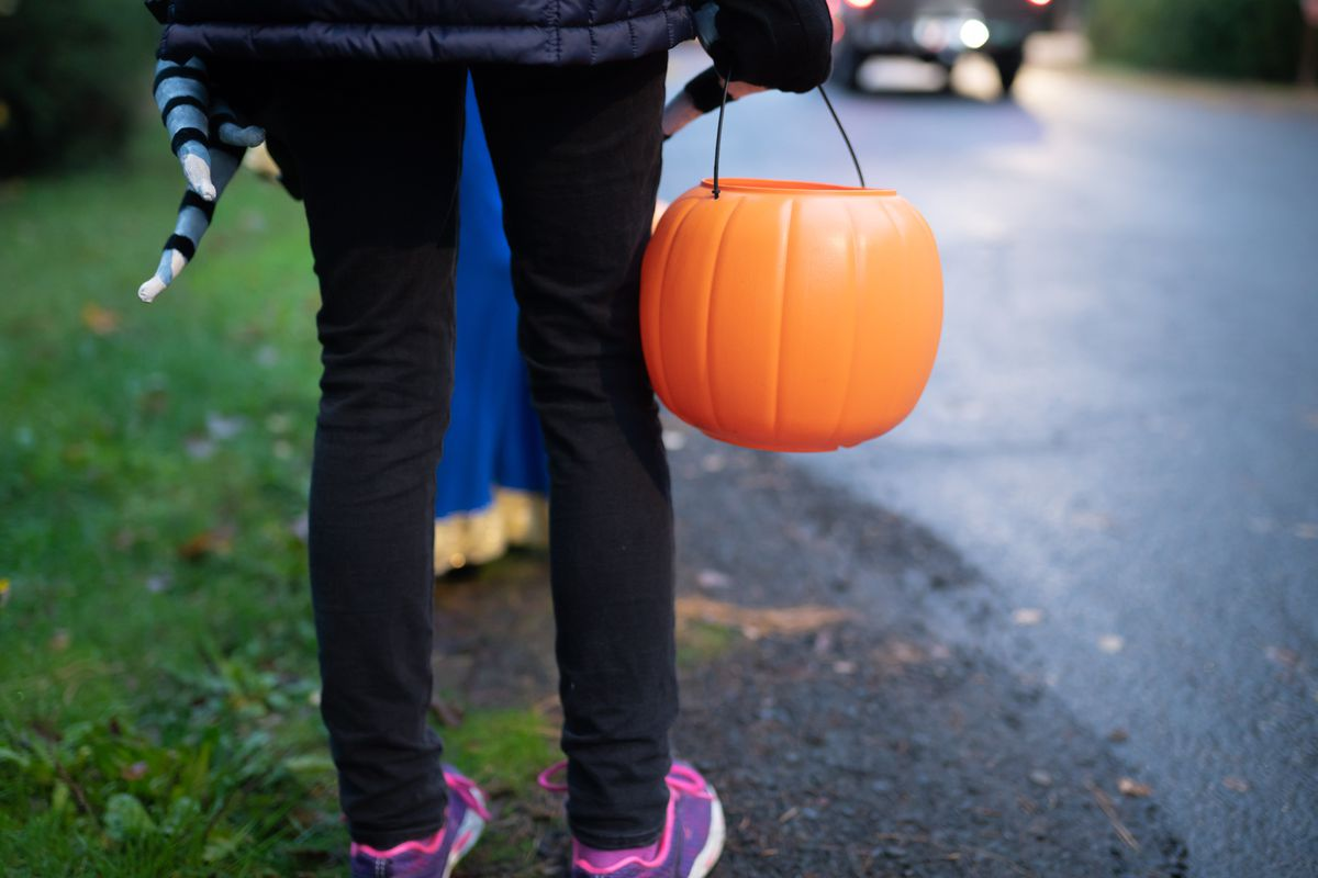 A person holding a trick or treat pumpkin is standing with two children in brightly colored costumes at the edge of as street as a car drives by.