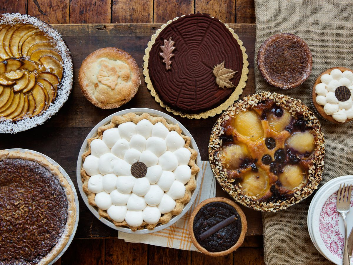 Bird's eye view of a variety of pies, from apple to the far left to a marshmellow-topped pumpkin one in the middle.