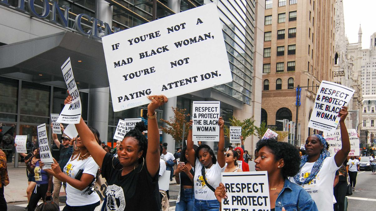 """Black women marching down a street holding signs that read, """"Respect & protect the black woman,"""" and, """"If you're not a mad black woman, you're not paying attention."""""""