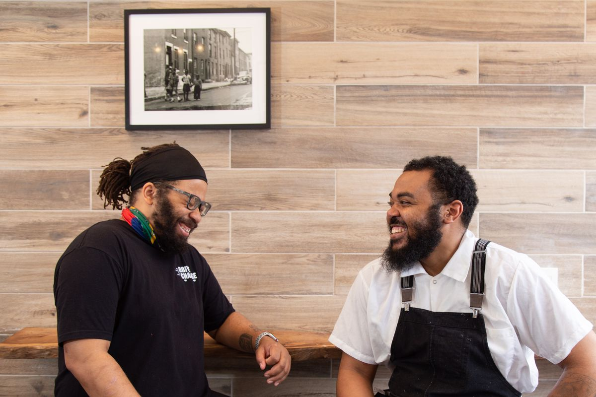 two men sitting at a counter laughing