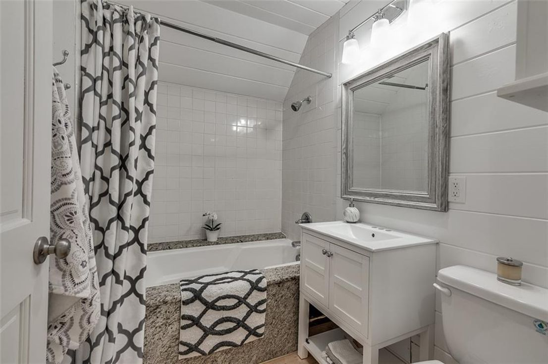 A white bathroom with a small tub and toilet at right.