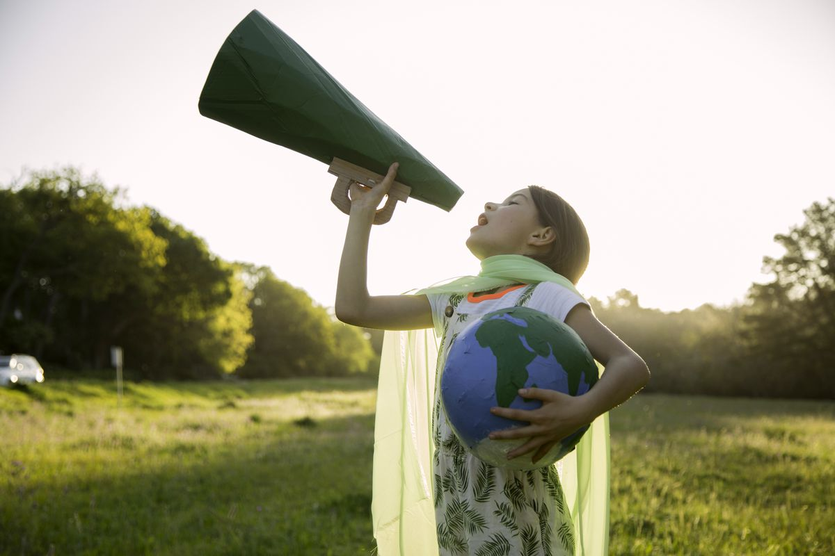 A young girl holds a green megaphone in one hand and clutches a globe resembling Earth in the other.