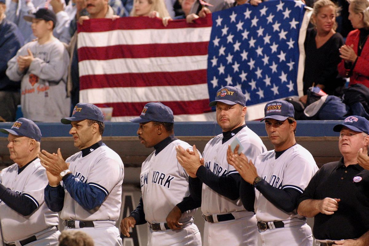 Members of the New York Yankees applaud as Chicago firefighters and police officers take the field prior to the Yankees game against the Chicago White Sox 18 September 2001 in Chicago. The game was the first for the two teams since Major League Baseball games were suspended for a period of mourning following the 11 September terrorist attacks.